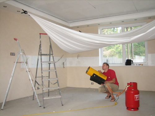 Натягивание полотна натяжного потолка