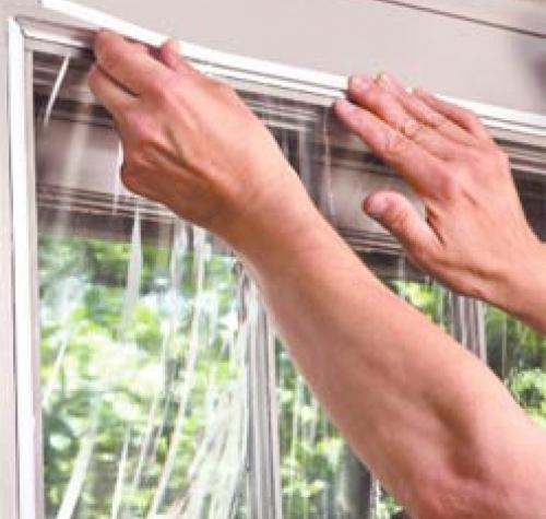 Наклеивание на окна теплосберегающей пленки